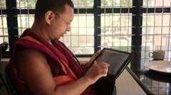 Happy Buddhist Monk going through photos in tablet Stock Footage