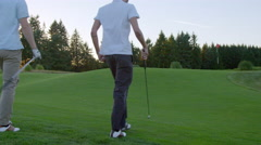 Two golfers walk to the putting green - stock footage