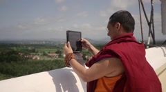 Buddhist Monk taking photo from top of monastery Stock Footage