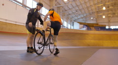 4K Competitive cyclist with prosthetic leg, practicing with trainer in velodrome Arkistovideo