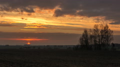 4k timelapse of sunrise over field and trees. - stock footage