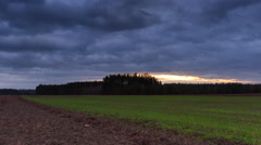4k timelapse of field under cloudy sky after sunset Stock Footage