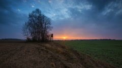 4k timelapse of sunrise over fields and raised hide and trees Stock Footage