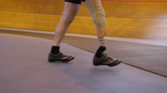 4K Competitive cyclist with prosthetic leg, practicing with trainer in velodrome Stock Footage