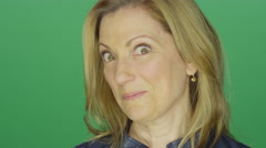 Middle aged woman making funny faces, on a green screen background Stock Footage