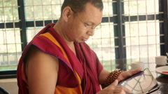 Buddhist Monk playing with tablet Stock Footage