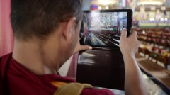 Buddhist Monk taking photo with his tablet inside temple Stock Footage