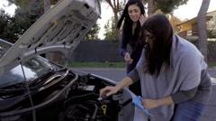 Women looking broken car engine on street asking for help medium shot Stock Footage