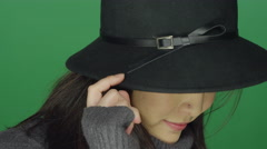 Beautiful young Asian woman in a hat flirting, on a green screen background Stock Footage