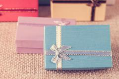 Small gift box set on sack cloth - stock photo