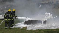 Firefighter dispense foam on burning container - stock footage