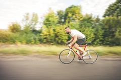 Young bearded hipster driving bicycle - stock photo