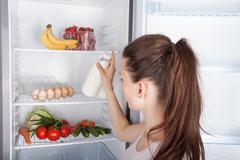 Woman chosen milk in opened refrigerator - stock photo