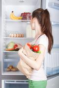 Woman near the refrigerator with healthy food. - stock photo