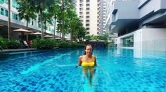 Girl in yellow swim suit relaxing in the big pool. Private propery Stock Footage