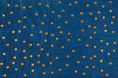 Abstract background with yellow rhinestones on denim - stock photo