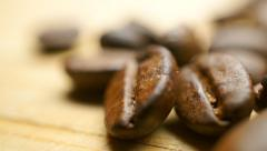 Pile of roasted coffee beans on light wooden table. Shallow focus macro pan shot Stock Footage