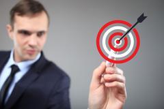 Goal and trigger concepts. Businessman click on virtual target Stock Photos