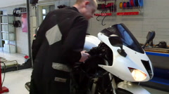 Mechanic is turning the gas handle on a motorcycle Stock Footage
