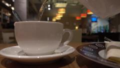 Pouring tea from teapot in the cup in a cafe. 4K close up shot Stock Footage