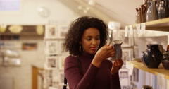 Young woman shopping and browsing at a pottery shop. Slow motion. - stock footage