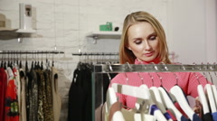 Young woman choosing clothes on a rack in a showroom Stock Footage