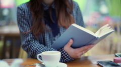 Woman reading book and drinking beverage in the cafe, steadycam shot Stock Footage