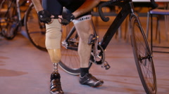 4K Man with prosthetic leg at cycling track attaches limb and prepares to train - stock footage