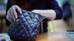 Woman looking for something in her bag while sitting at the table Stock Footage