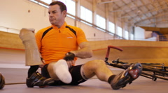 4K Man with prosthetic leg at cycling track attaches limb and prepares to train Stock Footage
