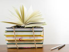 A stack of colorful books, open book - stock photo