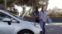 Women looking broken car engine on street asking for help Stock Footage
