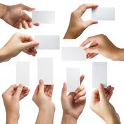 Hand holding white blank business visit card, gift, ticket, pass, present - stock photo
