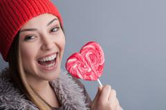 Attractive healthy woman is enjoying tasty candy - stock photo