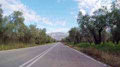 Olive groves vehicle drive POV country road trees plantation car blue sky - stock footage