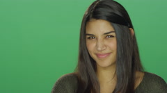 Young woman smiling, on a green screen studio background - stock footage