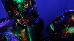 Man and woman in makeup glow in ultraviolet light Stock Footage