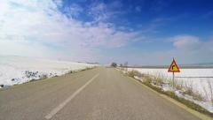 Vehicle driving winter countryside scenery snow road valley clouds blue sky POV - stock footage