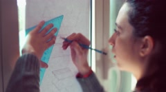 Teen girl tracing lines on plan - stock footage