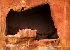 big hole in rusty steel plate - stock photo