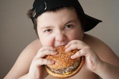 Boy kid fat  burger food  health sports cap hungry Stock Photos