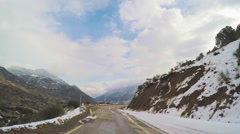 POV mountain road car vehicle drive countryside winter rural scenery snow clouds Stock Footage