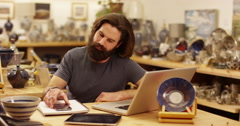 An attractive store owner working on a laptop. Slow motion. - stock footage