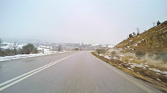 Winter countryside vehicle car drive road snow valley trees cloudy sky white POV Stock Footage