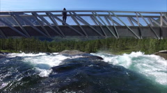 Flight under the bridge above waterfall in Norway Stock Footage
