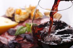 Pouring wine into glass and food background - stock photo
