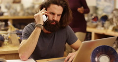 Stressed and worried small business owner talking on the phone. Slow motion. - stock footage
