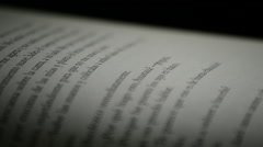 Pages and texts of open book rotating at black background Stock Footage