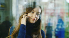Young woman at the glass storefront.  Concept - a foretaste of shopping Stock Footage