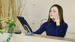 A young woman working at the reception or the hotel company - stock footage